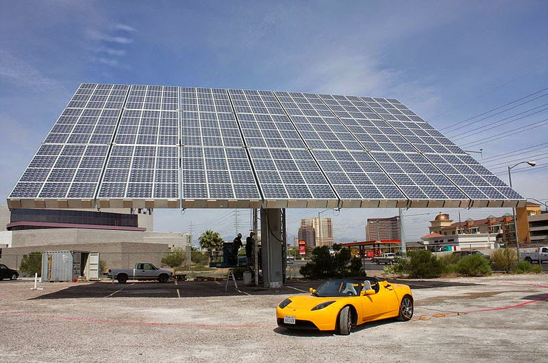 Tesla EV in front of solar panels
