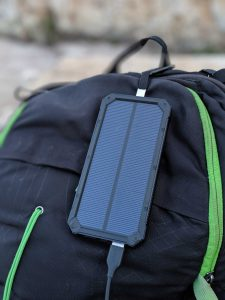 portable solar phone charger hanging from a backpack